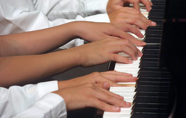 Children's hands playing the piano