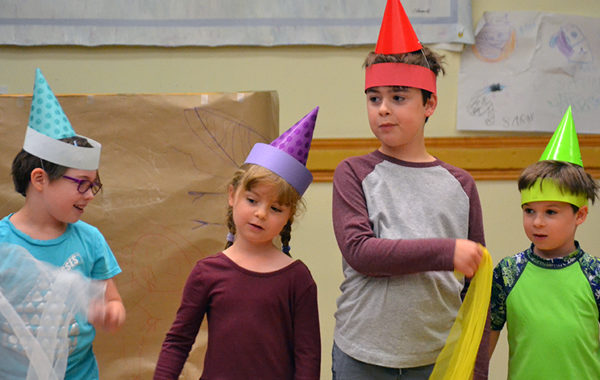 Young children wearing colorful hats.