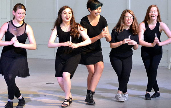 Teens performing a musical dance number.