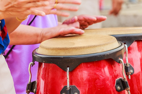 Hands drumming on a conga drum.