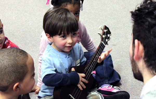 Young child playing the ukulele.