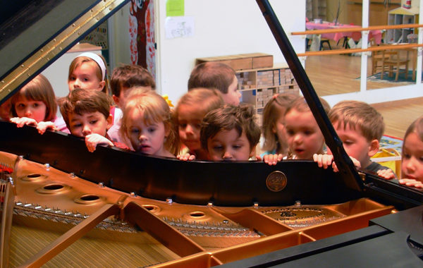 Preschoolers looking inside a piano.