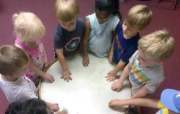 Preschoolers playing a large hand drum.