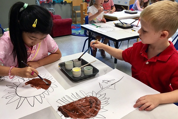 Young children painting in a class.